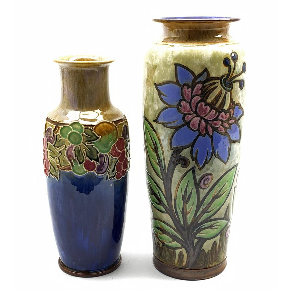 Royal Doulton vase of tapering form decorated with flowers and leaves, artists mark 'HG' H36cm and another with a band of berries on a blue ground, artist mark 'MW' H31cm