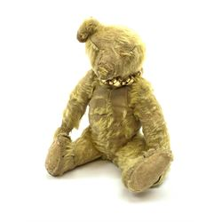 Early 20th century English teddy bear, with wood wool filled body with jointed limbs, felt covered paw pads, five claw stitching to feet and elongated arms with spoon shaped paws H14