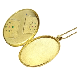 Heavy 18ct gold ruby, emerald and sapphire locket with engraved bird of paradise, perched on a branch hallmarked, on 18ct gold chain stamped 750