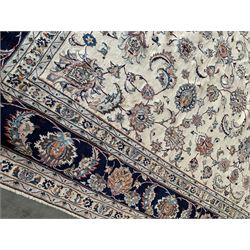 Large Persian Heriz carpet, ivory ground with trailing floral design and decorated with stylised flower heads, matching design to blue ground boarder, multiple guards with foliate decoration