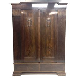 Early to mid 20th century oak double wardrobe, the interior fitted with hanging space and shelves, two drawers to base, shaped bracket feet