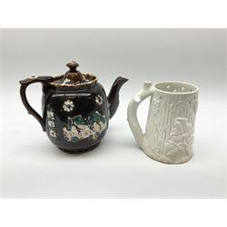 A 19th century Barge Ware teapot, decorated with applied floral sprays and thistles against a mottled brown ground, and plaque detailed Catherine Taylor God Bless Our Home 1890, H18cm, together with a white glazed puzzle mug, H15cm.
