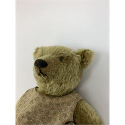 Early 20th century German Steiff teddy bear c1910 with wood wool filled humped back mohair body, swivel jointed head with black boot button eyes and horizontally stitched black nose and mouth, FF metal button to left ear, jointed elongated limbs with felt paw pads and black stitched claws H13
