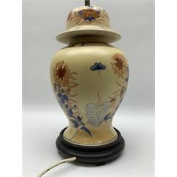 An Oriental style table lamp modelled as a ginger jar, with foliate decoration in blue and red, including fixtures H43.5cm.
