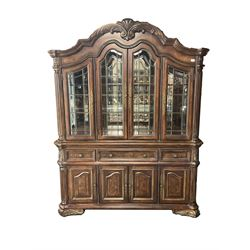 Kevin Charles American walnut display cabinet, illuminated interior, shell carved pediment above four bevel edge doors enclosing six glazed shelves above one central long drawer flanked by two short drawers, above three cupboards, carved bracket supports
