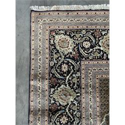 Large Fine Persian Tabriz carpet, dark blue field profusely decorated with small Herati motifs and large cusped pole medallion with matching spandrels, multiple guarded border, the main band decorated with trailing foliage design and stylised leaf and flower head motifs