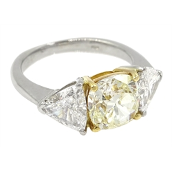 Platinum three stone diamond ring, the centre fancy light yellow cushion cut diamond of approx 1.70 carat with two white trillion cut diamonds either side, each weighing approx 0.60 carat, hallmarked, total carat weight approx 2.90 carat
