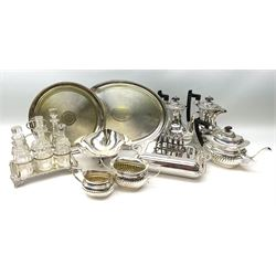 A silver plated six bottle cruet stand, upon four scroll feet, together with other silver plate, to include a five piece silver plated coffee set, two trays, etc.