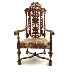 20th century Carolean style carved oak armchair, the back carved with scrolls and foliage, lobe carved supports joined by curved x-frame stretchers