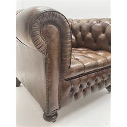 Large pair of Country House chesterfield club armchairs of generous proportions, upholstered in deeply buttoned brown leather, turned front supports with castors, rear splayed supports