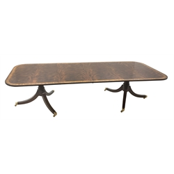 Regency style figured mahogany dining table, rounded rectangular crossbanded top with ebonised stringing, pull out extending action, two additional leaves, on turned  twin pedestal base each with three out splayed supports and brass cups and castors, H74cm, 123cm x 199cm - 320cm (extended)