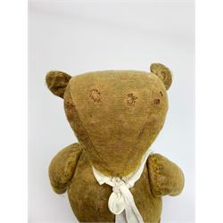 Early 20th century English teddy bear c1920 with wood wool filled body, jointed swivel head with glass eyes and horizontal stitched nose and mouth, jointed limbs and inoperative growler mechanism H23