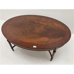 Cross banded mahogany oval coffee table, turned and moulded supports joined by shaped stretcher