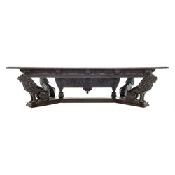 Large 19th century carved oak library table, the rectangular top with lunette carved edge over cartouche panelled and carved  scroll frieze, the central tapering rectangular support relief carved with masks and garlands, on four carved seated lion supports at each corner, on flat angular stretcher with recessed castors stamped 'Bartholomew & Fletcher, London'