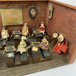 Late Victorian wooden school room setting with bisque head teacher and six German all bisque pupils each seated at a combined desk and chair with slate board, in a classroom furnished with chest of drawers, fire-surround, lectern, wall map, pictures, miniature books, school bell, chalk board on easel, wall clock etc, L70cm H28cm D28cm