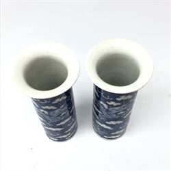 Pair of late 19th/early 20th century Chinese cylindrical vases each decorated with dragons chasing the flaming pearl amongst clouds, underglaze blue four character mark H21cm
