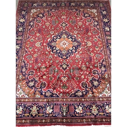 Kashan red ground rug carpet, the field decorated with scrolling stylised foliage with central medallion, repeating blur ground border with flower head guard, 390cm x 295cm