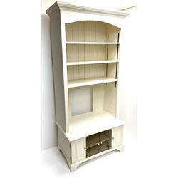 Cream painted bookcase on media stand, projecting cornice, three adjustable shelves above two glazed doors flanked by two cupboards, bracket supports