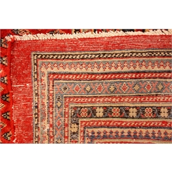 Araak red ground rug, field decorated with repeating Boteh motifs, graduated multicoloured striped geometric border, 364cm x 270cm
