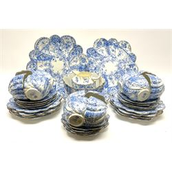 An Edwardian Chapman teaset, of lobed form decorated with blue transfer printed foliate decoration, comprising twelve cups, twelve saucers, nine side plates, and two cake plates.