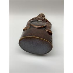 A treacle glazed stoneware bottle modelled as a man seated upon a barrel, not including cork stopper H24cm.