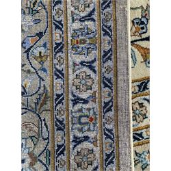 Large Fine Kashan carpet, ivory ground with interacting foliate designs and decorated with stylised flower heads, the multiple banded border decorated with scrolling foliage design with matching stylised flower heads, the outer guard signed by the weaver