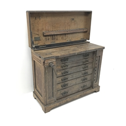 Late 19th century work bench tool cabinet, hinged lid enclosing tool rack, single vice, six graduating drawers, storage cupboards at both ends, inlaid Melhusih plaques,  shaped plinth base by Richard Melhuish & Sons, London(W107cm, H88cm, D50cm) and a quantity of hand tools