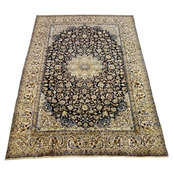 Persian Nain carpet, floral design on dark blue field, central rosette medallion, ivory ground outer border, 430cm x 305cm