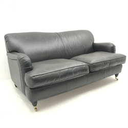 Three seat traditional sofa upholstered in black leather, turned supports, W184cm