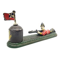 Very rare 19th century John Harper & Co. mechanical cast-iron money box, registered number 33821 patented 1885, inscribed on metal plaque 'Wimbledon Bank', based on the Queen's Trophy for shooting at Wimbledon, depicting a British Infantry man in red tunic and blue trousers lying on the ground using a gun to fire a brass coin launcher into a pill box with removable moving flag above L30cm