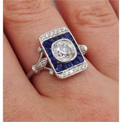 White gold cushion cut diamond, calibre cut sapphire and diamond diamond panel ring, stamped 18K, the central diamond approx 0.90 carat