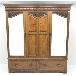 Early 20th century carved oak triple wardrobe, with two shaped mirrored doors, two drawers to base with Art Nouveau copper handles, W189cm, D50cm, H210cm