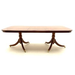 Yew wood twin pedestal extending dining table, shaped supports and brass castors (W216cm, D100cm, H77cm) and six (4+2) chairs, shaped back and upholstered in patterned fabric raised on fluted supports (W52cm)