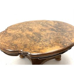 Victorian and later highly figured walnut table, shaped moulded tilt top with quarter matched veneer, the skirt decorated with carved scroll mounts, faceted baluster column on platform, turned feet with recessed castors