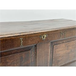 18th century oak coffer, moulded rectangular hinged lid, the frieze rail set with studded initials 'I.M' and engraved brass plate escutcheon, double fielded panel front, lower applied mould, on stile supports