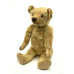 1930s teddy bear, possibly Farnell, with wood wool filled blond mohair body, the revolving head with original clear glass eyes, shaved muzzle with vertically stitched nose and mouth and jointed limbs with five-stitch claws H18.5