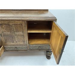 Early 20th century oak sideboard, raised back featuring carved detail, three panelled cupboard doors enclosing fitted interior, above three long drawers, raised on carved cup and cover supports to meet stetcher