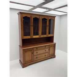 Large teak wall cabinet, projecting cornice, fitted with two double glazed doors enclosing glazed shelving, below unit is fitted with three long graduating drawers, flanked by two cupboards enclosing more shelving, raised on shaped bracket supports