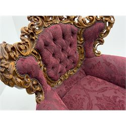 Late 20th century Italian style carved beech framed three seat sofa and pair matching armchairs, the framed carved and pierced with scrolling acanthus leaves and flower heads, cabriole supports, upholstered in buttoned claret fabric with raised foliate pattern