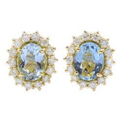 Pair of 18ct gold oval aquamarine and diamond cluster stud earrings, hallmarked, total aquamarine weight approx 1.65 carat, total diamond weight approx 0.55 carat