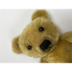 Merrythought Hygienic Toys large 'Magnet' teddy bear c1930s with plush body, swivel jointed head with glass eyes and vertically stitched nose and mouth and jointed limbs,  celluloid wishbone button to right ear and stitched label under right pad H22